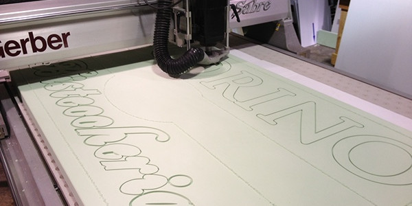 "After rendering the customer's sketch with design software, we translate the sign's elements into toolpaths with a CNC machining program. Our computerized router follows the paths and carves a raw piece of 2"" thick high density urethane foam. This sign is approximately 7' x 4'."
