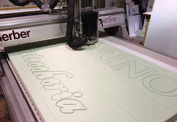 """After rendering the customer's sketch with design software, we translate the sign's elements into toolpaths with a CNC machining program. Our computerized router follows the paths and carves a raw piece of 2"""" thick high density urethane foam. This sign is approximately 7' x 4'."""
