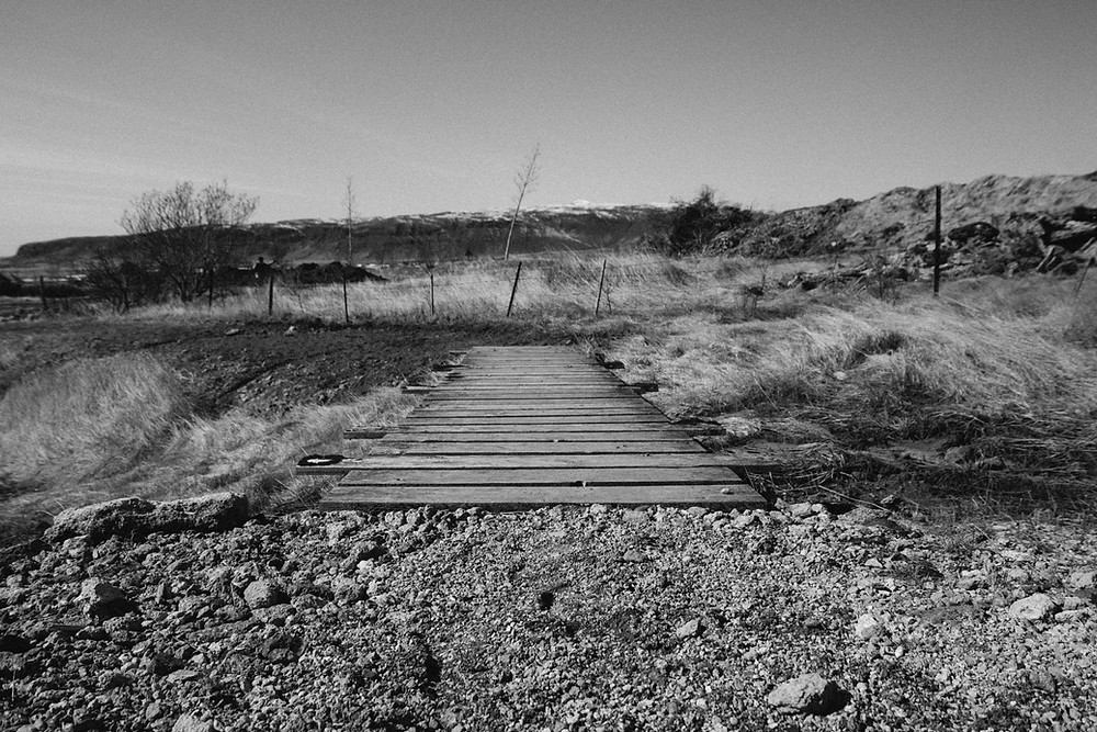 black and white photo of bridge in rural setting