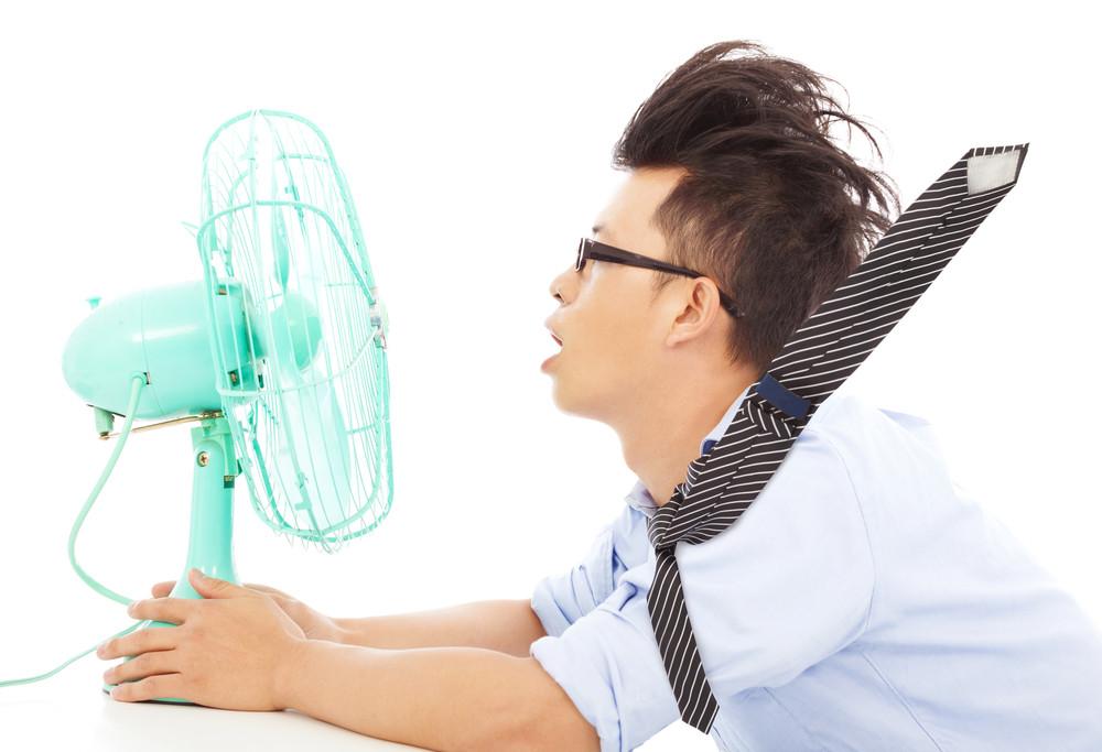 Summer heat, man in front of fan