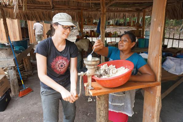Marie-Ève intenta moler el maíz con Doña María supervisando.