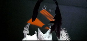 [Image description: A screen shot of Angélica's Zoom green screen glitch in which her skin overlaid/merged with a background picture of peach colored sunrise light casting shadows on a white ceiling. Her eyes, hand silhouette, straightened black hair, and white knitted sweater are distinct from the green screen background.]