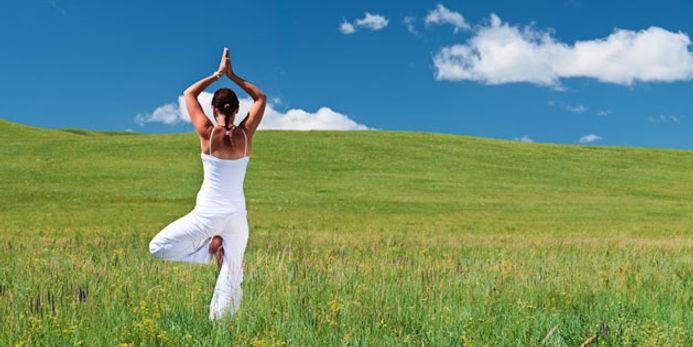fastende Frau welch Yoga auf einer Wiese macht