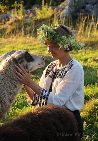 Kuvassa nuori nainen istuu hymyillen niityllä suuri kukkaseppele päässään ja silittää lampaan päätä. Lammas katsoo ihmiseen.