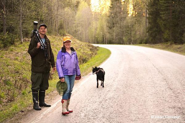 Kuvassa Pirteän Pässin asukkaat Risto ja Jaana Sulkava seisovat hymyillen tiellä koiransa Ursuksen kanssa. Ristolla on olalla kaukoputki.