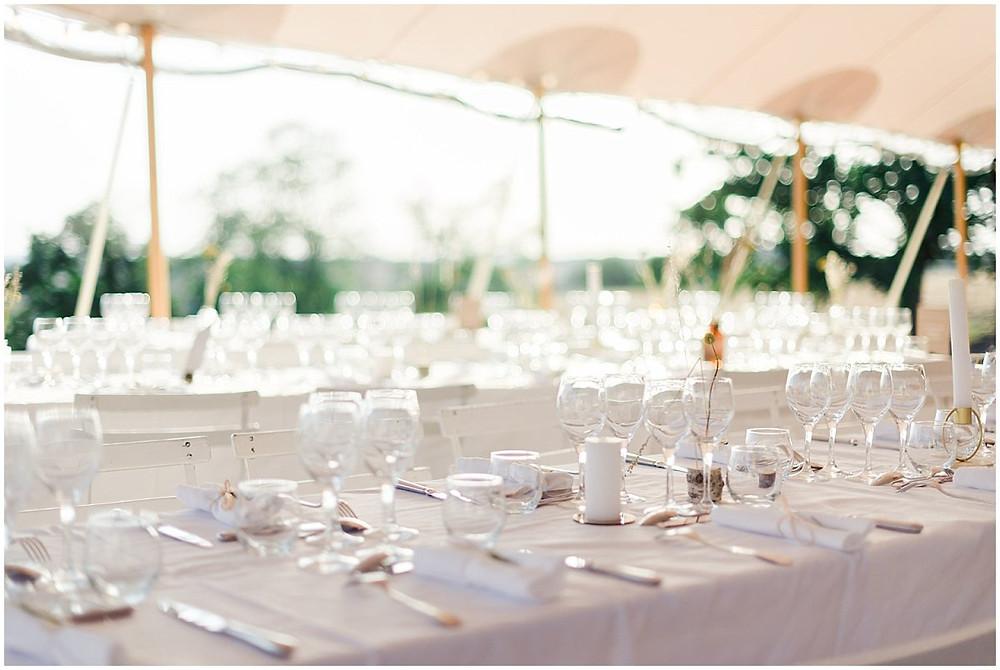 Cette image montre la décoration d'une table de mariage lors d'un mariage en extérieur, sous une tente, en Borugogne.