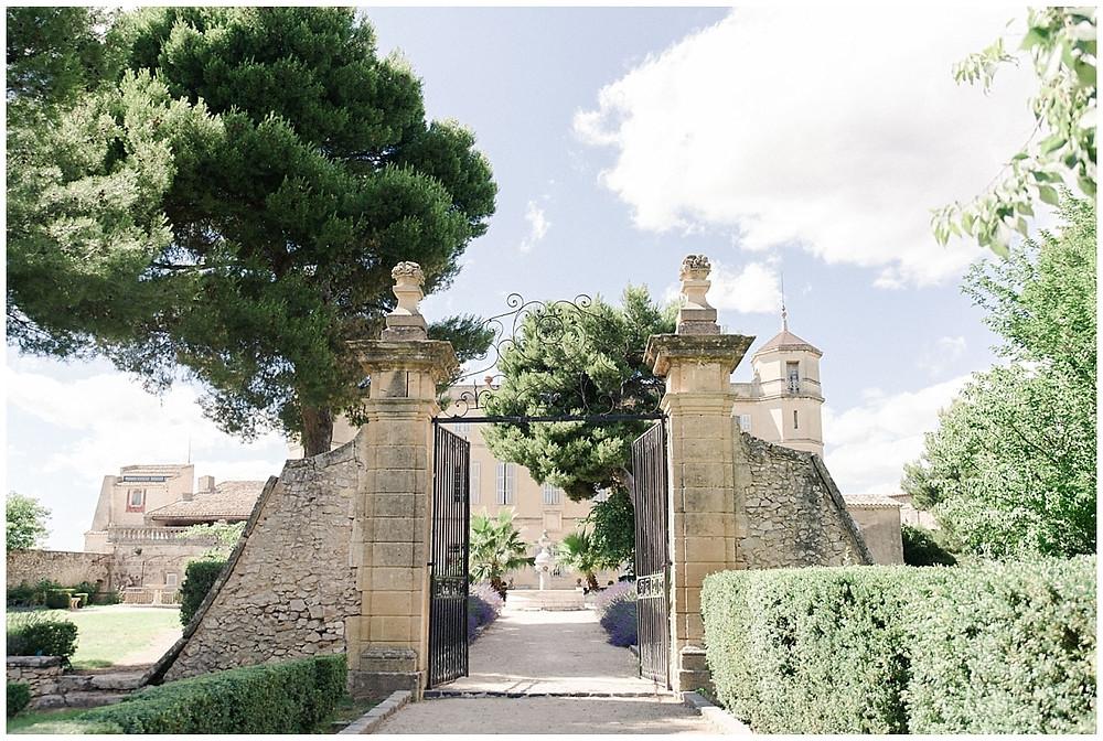 Portail d'entrée au Château de Sénéguier : le portail donne accès aux jardins à la française du Château. Du portail, on peut voir la fontaine d'où jaillit de l'eau de source. L'allée qui mène au Château est bordée de lavandes.