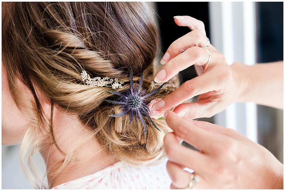 Photo de détail de la coiffeuse en train de terminer le chignon de la mariée : elle insère délicatement des fleurs fraiches pour orner le chignon.