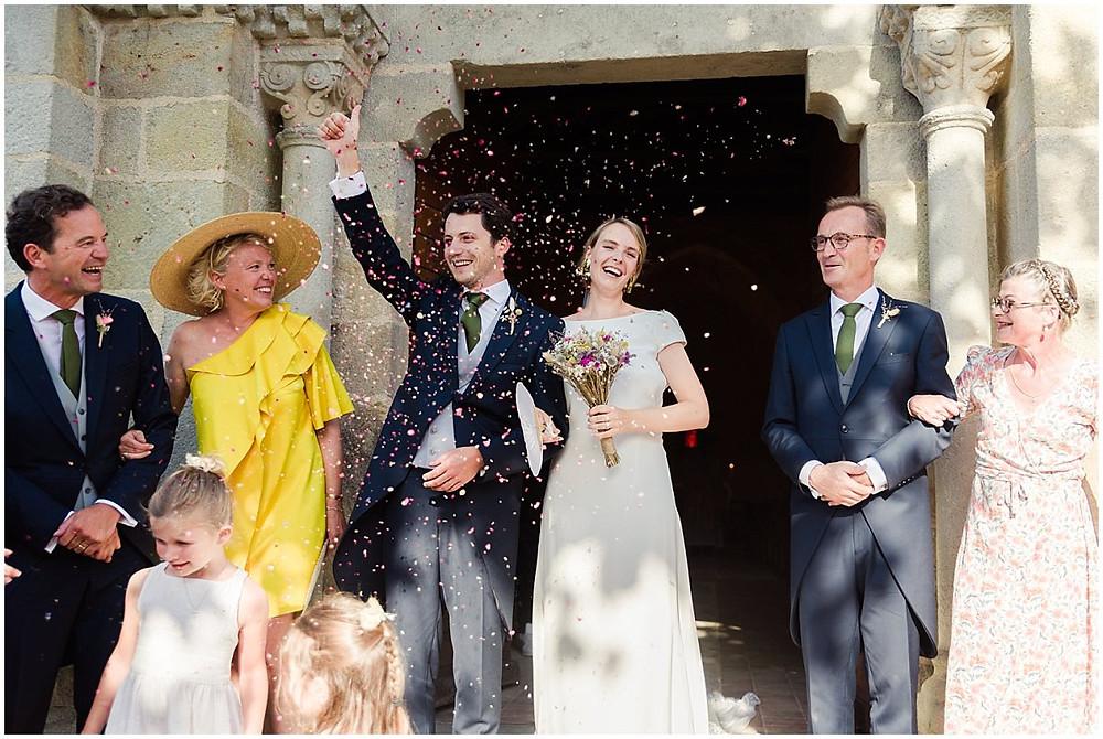 Sur cette photo, on peut voir la sortie d'église des mariés lors d'un mariage en Bourgogne. Ils sont entourés de leurs parents et sont très joyeux. Les enfants lancent des confettis.