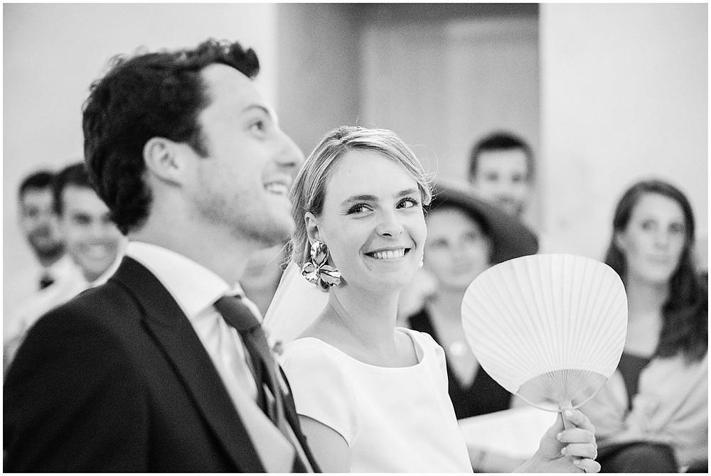 Sur cette photo, on peut voir un moment de complicité entre les mariés lors de la cérémonie religieuse à l'église en Bourgogne. La mariée regarde le marié avec un regard empli d'amour.