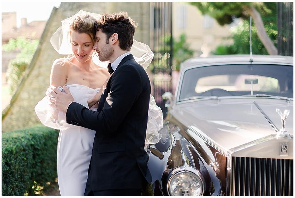 Les mariés s'enlacent dans l'allée du Château de Sénéguier en Provence. La voiture est mariés est une rolls royce.