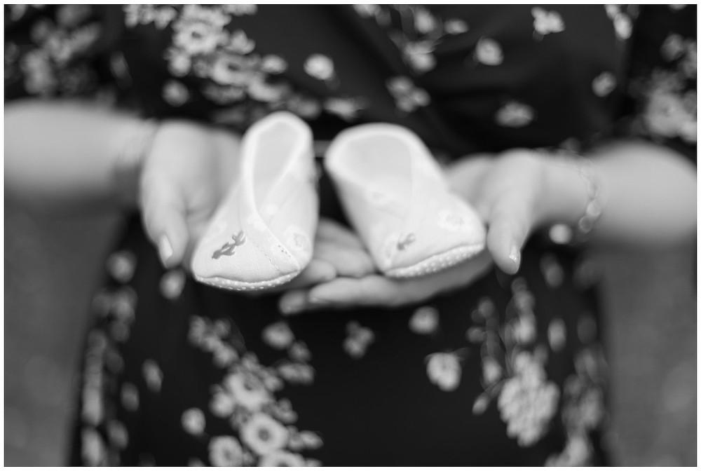 Sur cette photo, on voit la future maman porter les petits chaussons de son enfant à venir. Ce sont des petits chaussons d'inspiration japonaise. La photo est en noire est blanc.