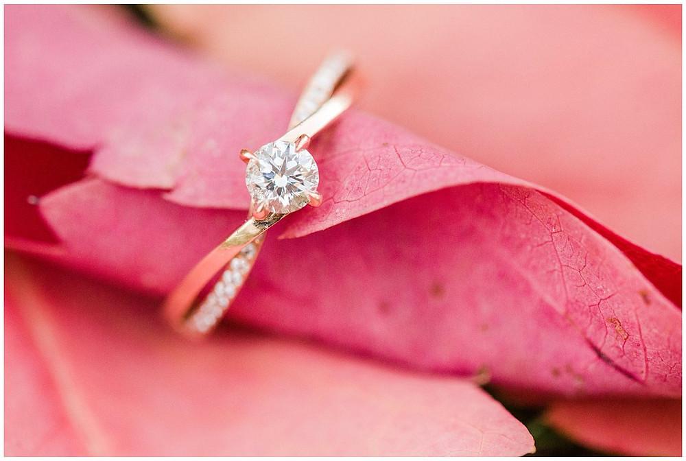 Sur cette image, on peut voir une bague de fiançailles en gros plan, posée sur des feuilles aux couleurs chatoyantes de l'automne. Il s'agit d'une bague qui a pour pierre principale un diamant, mais d'autres petits diamants jonchent le reste de l'anneau.