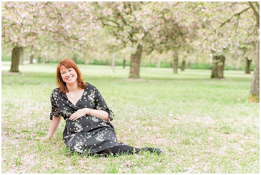 Une future maman est assise dans l'herbe sous les cerisiers en fleurs au Parc de Sceaux. C'est le printemps, elle porte une robe robe avec des pétales de fleurs roses dessus. La future maman est rousse. On voit les cerisiers en fleurs.