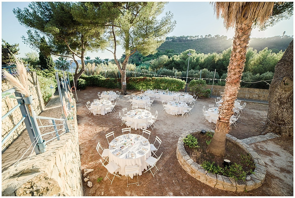 Dîner de mariage en extérieur à Saint-Mandrier-sur-Mer : le dîner de mariage se fera proche de la mer, des tables rondes ont été installées. Les nappes sont blanches.