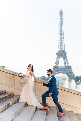 paris-wedding-photographer - Couple dressed in gown and tux walking up the stairs of Trocadero's place in front of the Eiffel Tower in Paris