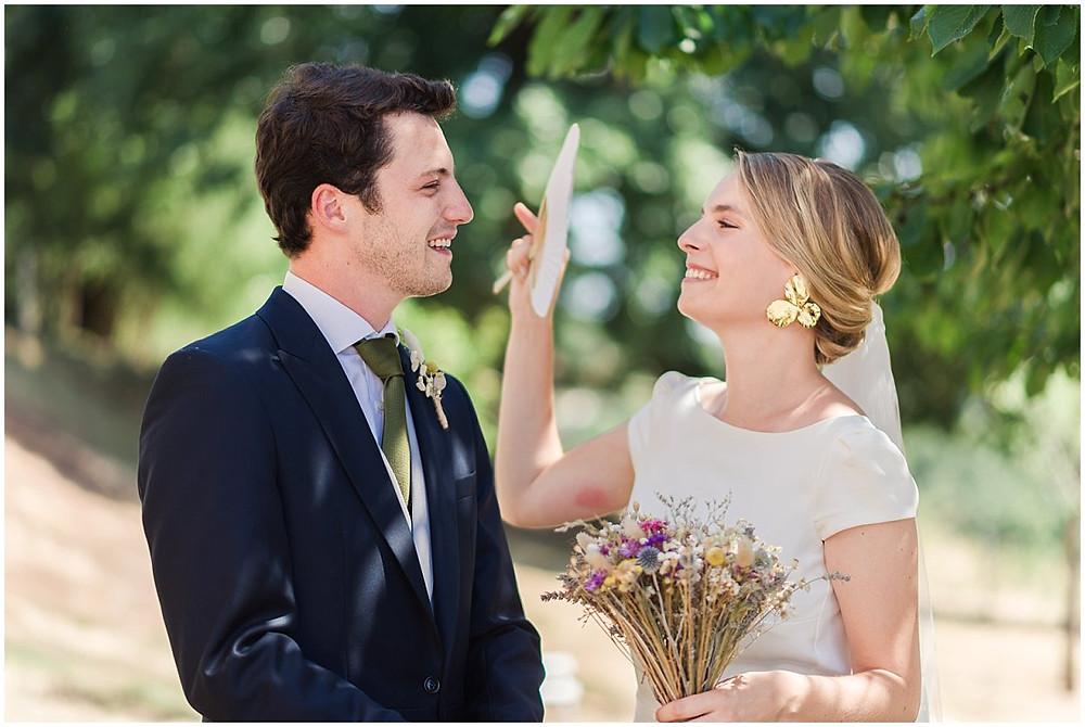 Il fait très chaud ce jour d'été en Bourgogne, la mariée a un éventail et s'amuse à faire de l'air pour le marié. Ils sourient tous les deux.