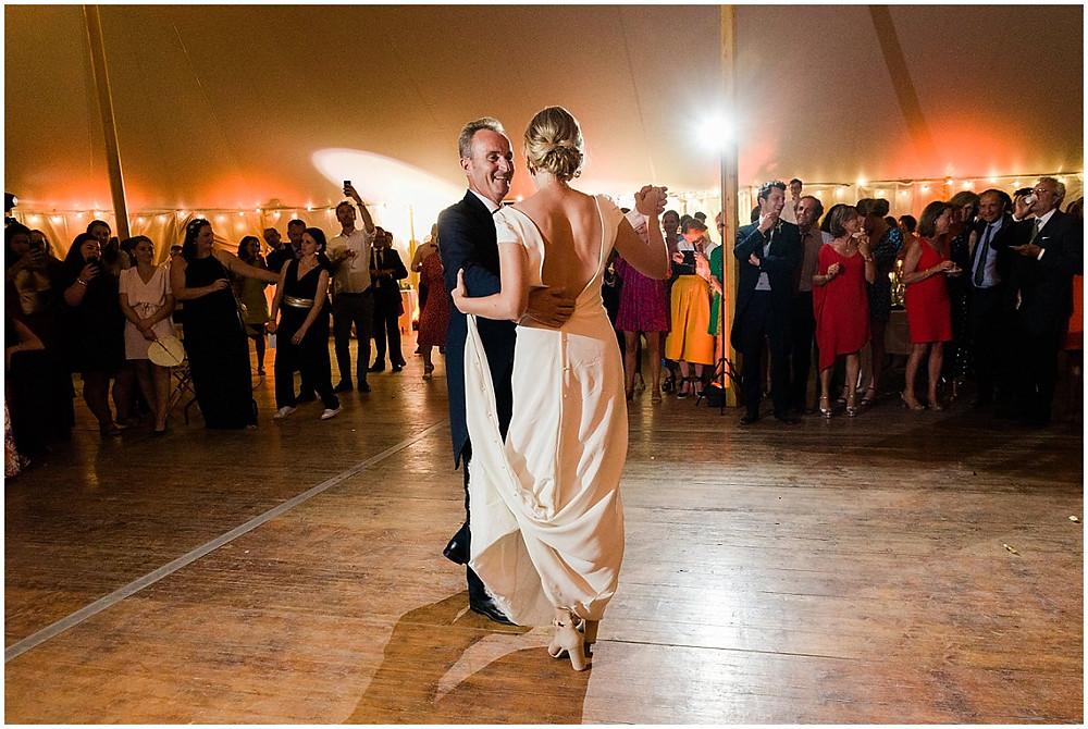 La mariée ouvre le bal avec son père. Les invités sont réunis tout autour de la piste de danse pour assister à l'ouverture de bal.