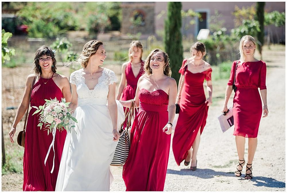 La mariée et ses demoiselles d'honneur toutes vêtues de rouge se dirigent à pied vers le marié : on arrive bientôt au moment du first look entre le marié et la mariée.