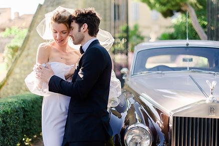 photographe mariage manche - couple enlacé en robe et costume devant l'entrée d'un château provencal proche d'une Rolls Royce beige et brune à Saint-Lô dans la Manche