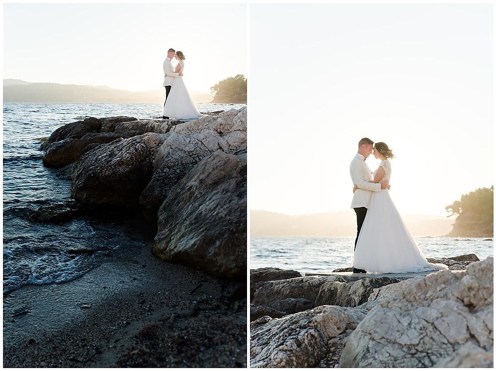 Séance de photo de couple au bord de la mer lors d'un mariage à Saint-Mandrier-sur-mer : la plage au coucher du soleil est un lieu idéal pour des photos de couple magnifiques. Les mariés sont placés sur les rochers au bord de l'eau, front contre front, et s'enlacent tendrement.