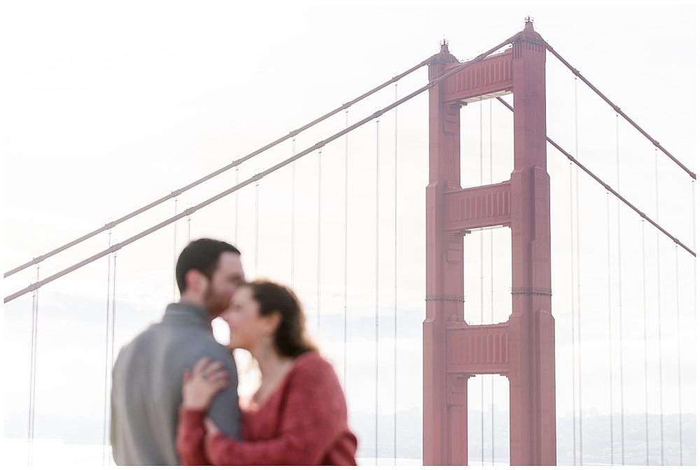 Le couple s'enlace devant le golden gate bridge.