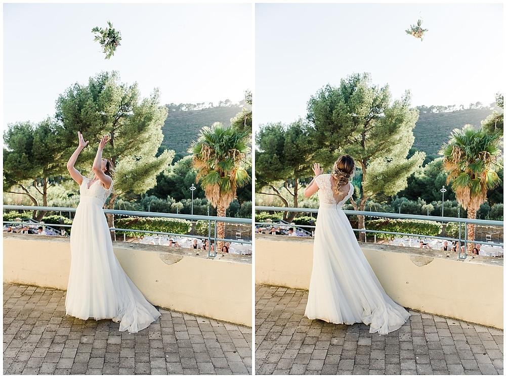 La mariée lance le bouquet depuis un endroit surélevé : le bouquet vole dans les airs. La mariée regarde le bouquet redescendre.