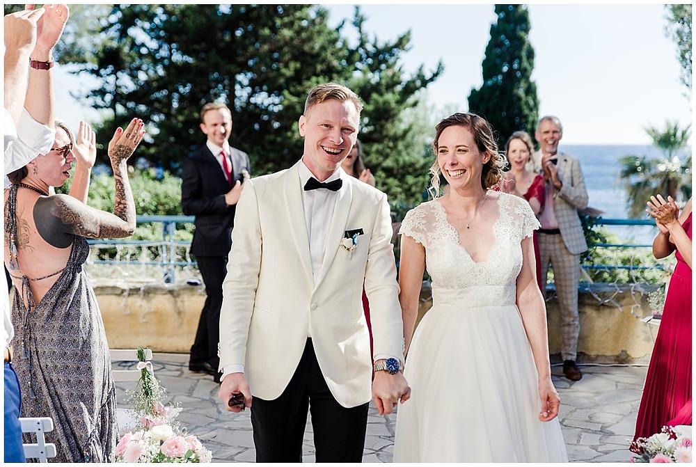 Portrait des mariés quittant le lieu de cérémonie de mariage sous les acclamations de leurs invités.