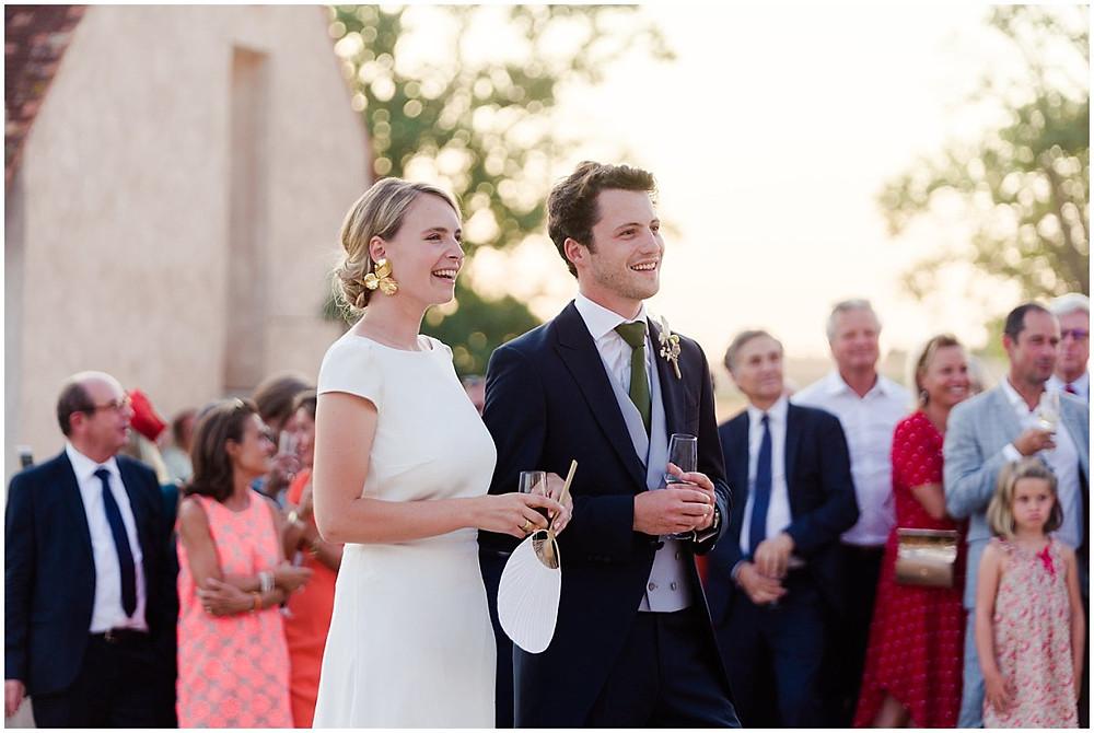 Lors du cocktail de leur mariage en Bourgogne, les mariés écoutent les discours de leurs pères. Ils se tiennent l'un à côté de l'autre, les invités sont en arrière plan.