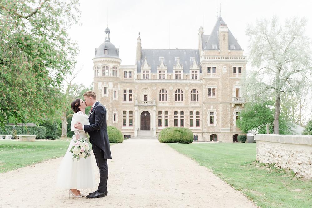 Sur cette image, on peut voir un couple de jeunes mariés. Ils se tiennent l'un en face de l'autre dans la cour du château de Méridon dans les Yvelines et s'embrassent. Le marié porte un costume queue de pie gris. La mariée porte une robe mi-longue ornée de dentelles ainsi qu'une étoile pour couvrir ses épaules. Son bouquet est dans les tons pastels rose et blanc.