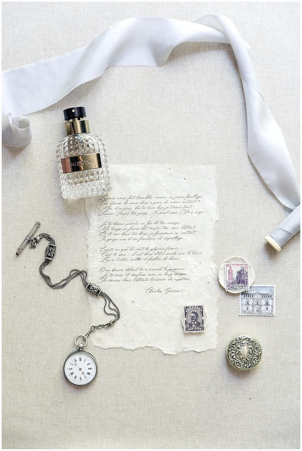 Photo des détails du marié lors du mariage au Château de Sénéguier: il s'agit d'une montre à gousset, d'un parfum, d'une lettre.