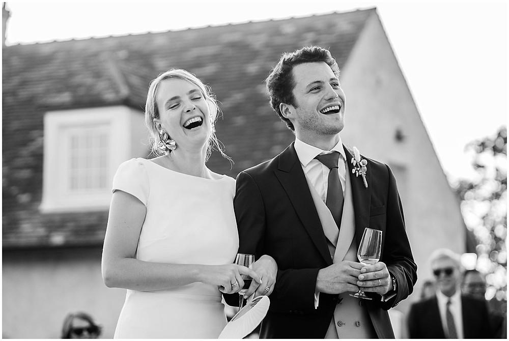 Sur cette photo, on peut voir les mariés éclater de rire à l'écoute des discours de leurs pères.