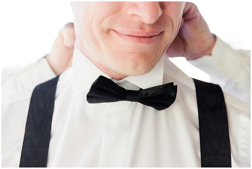 Photo de détail du marié : son témoin ajuste son nœud papillon.