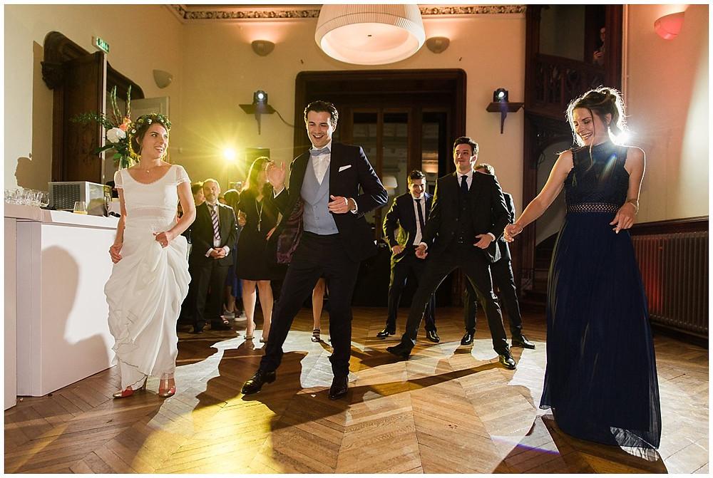 Sur cette image, on peut voir une ouverture de bal lors d'un mariage. Les mariés sont entourés de leurs témoins sur la piste de danse et exécutent une chorégraphie. La mariée porte une robe fluide, le marié un costume bleu avec un gilet bleu clair.