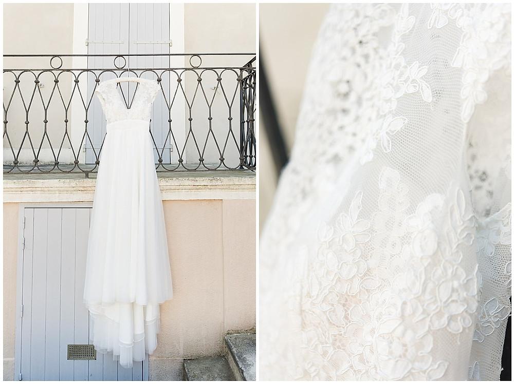 Photos de la robe de la mariée : il s'agit d'une robe de la marque Cymbeline. Elle est accrochée dehors, au balcon du bâtiment. C'est une robe fluide, douce, avec de la dentelle sur le buste.