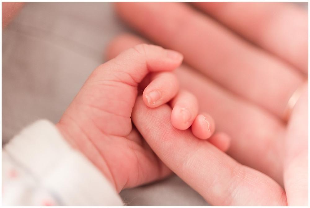 Photo de détail lors d'une séance photo naissance lifestyle à Evreux : le bébé tient le doigt de sa maman.