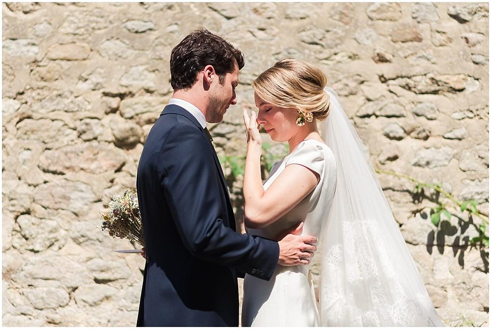 Cette photo montre le moment très émouvant de la découverte des mariés avant la cérémonie. La mariée essuie une larme, le marié la tient dans ses bras.