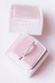 photographe mariage nord - Boite à alliance en velours rose pâle sur fond rose poudré contenant une aliance tour de diamants en or blanc à Lille dans le Nord