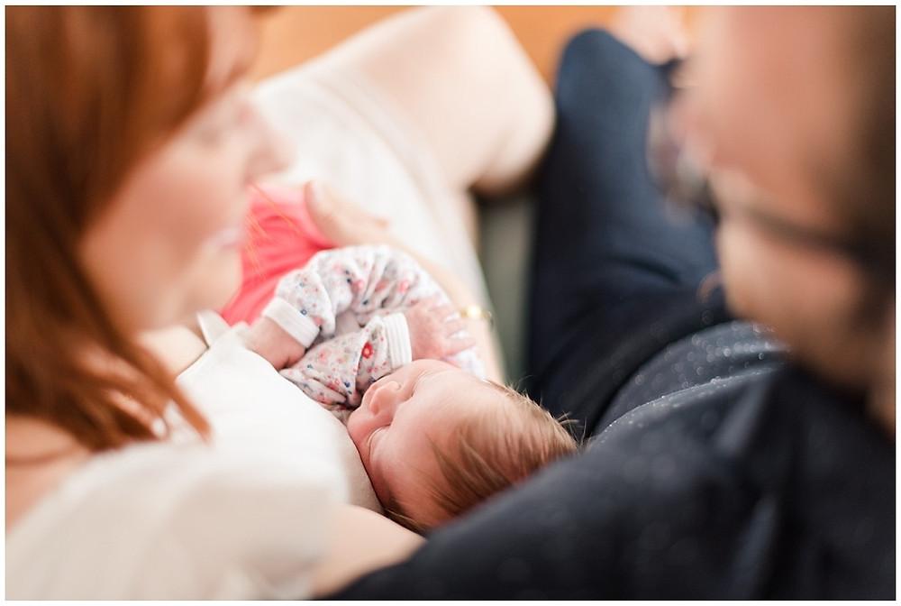 Cette photo montre un nouveau-né dans les bras de ses parents lors d'une séance photo naissance lifestyle à domicile, à Evreux.