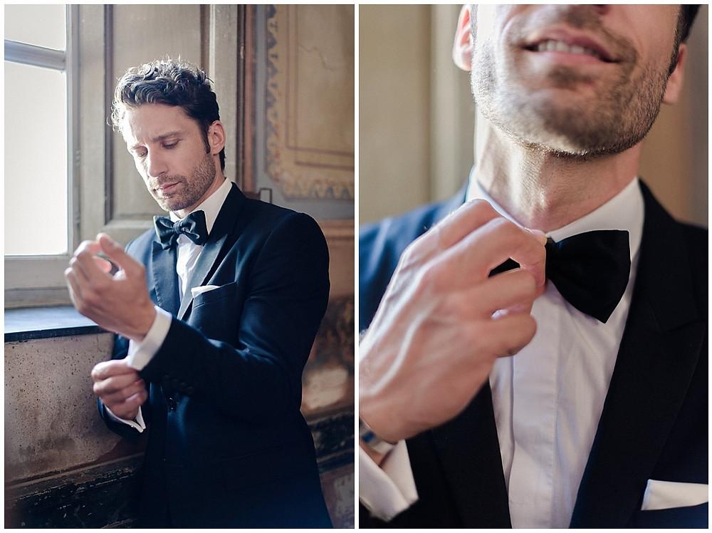 Portrait du marié dans l'entrée du Château Sénéguier : il ajuste ses boutons de manchette et son nœud papillon. Il est vêtu d'un smoking noir.