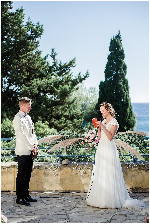Les mariés échangent leurs vœux lors de la cérémonie laïque de mariage sur la terrasse à Saint-mandrier-sur-Mer. Les mariés sont l'un en face de l'autre avec la mer en arrière-plan.