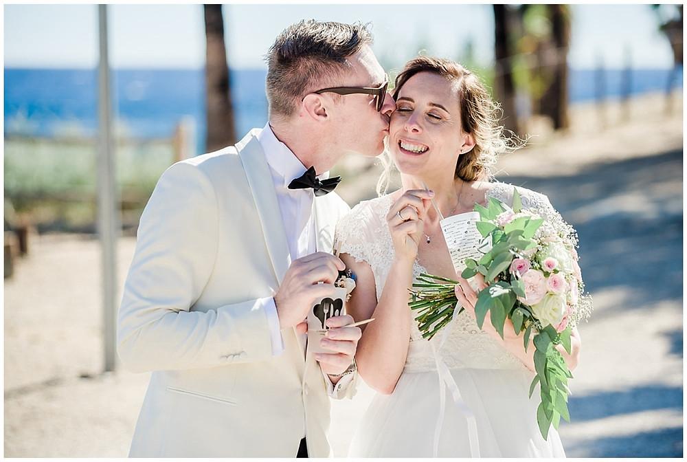 Les mariés profitent d'un temps calme avant la cérémonie : ils boivent un verre de citronnade en bord de mer. Le marié embrasse sa femme sur la joue.