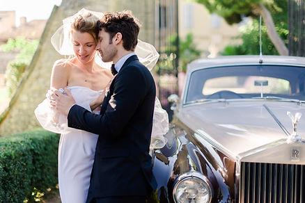 couple enlassé en robe et costume devant l'entrée d'un château provencal proche d'une Rolls Royce beige et brune à Vannes dans le Morbihan