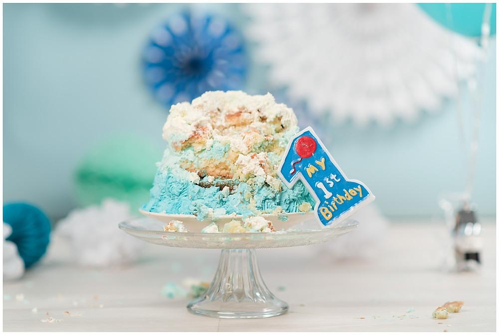 Sur cette image, on voit le gâteau d'anniversaire à la fin de la séance photo smash the cake. Le gâteau est éclaté, l'enfant a bien profité de sa séance photo.