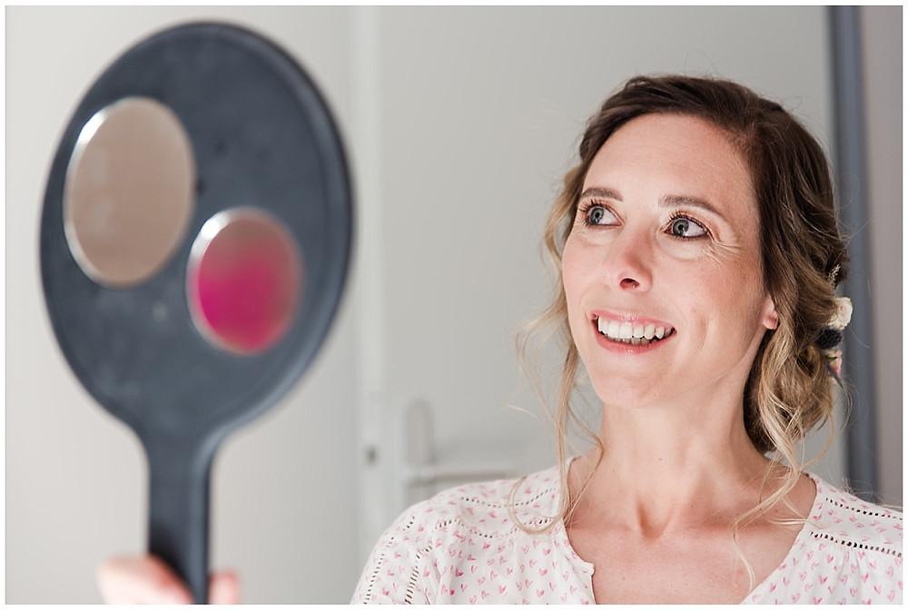 Portrait de la mariée suite à sa coiffure et son maquillage : la mariée se regarde dans le miroir de la maquilleuse, elle sourit.