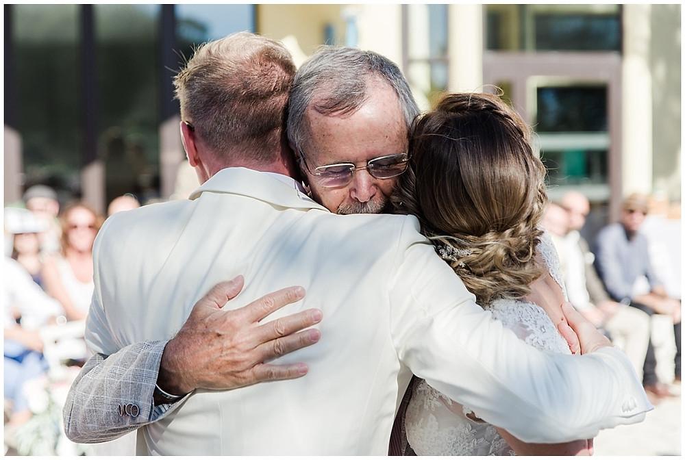 Le père se la mariée serre sa fille ainsi que son futur gendre sans ses bras.
