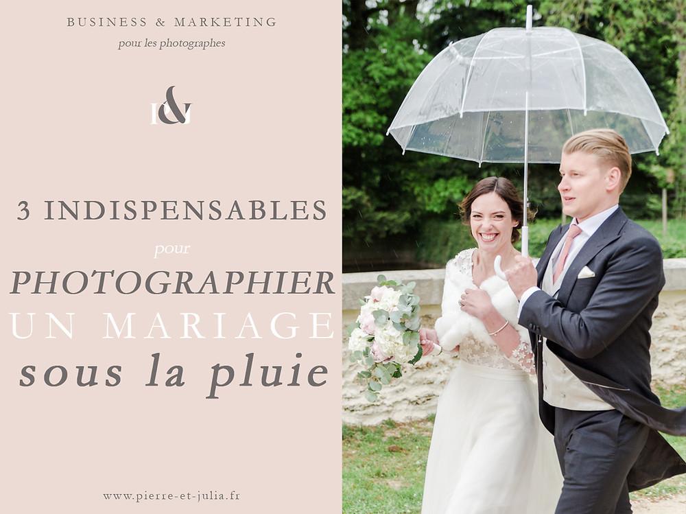 """Sur cette image, on peut voir une photo ainsi que du texte. Le texte indique """"3 indispensables pour photographier un mariage sous la pluie"""". Sur la photo, on peut voir un couple de jeunes mariés sous la pluie. Ils marchent et tiennent un parapluie transparent. Le marié porte un costume queue de pie et la mariée une robe mi-longue ornée de dentelle. Son bouquet de mariée est rose et blanc. Ils sont dans la cour d'un château."""