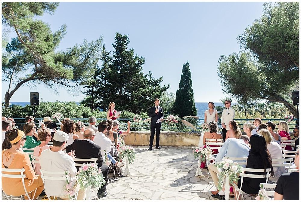 La cérémonie laïque débute : les officiants accueillent les mariés et leurs invités. La cérémonie se passe sur une terrasse avec vue sur la mer, à Saint-Mandrier-sur-Mer, dans le Var.