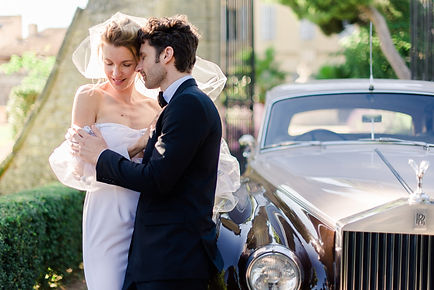 French Riviera wedding photographer - couple embracing in dress and costume in front of the entrance of a provencal castle near a beige and brown Rolls Royce next to Cannes in the French Riviera