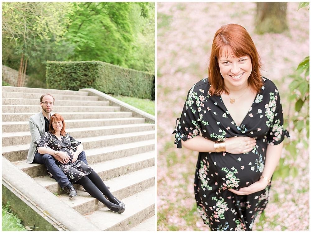 Sur cette image, on peut voir un portrait d'une femme enceinte. Cette femme enceinte est rousse, elle porte une robe noire avec des petites fleurs roses. Ses mains sont posées sur son ventre. C'est le printemps, le sol du parc de sceaux est jonché de pétales des cerisiers en fleurs. On peut également voir la future maman assise dans des escaliers avec le futur papa.